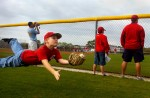 Cincinnati Reds fan Emerson Dietz, 10, dives to catch a ball he threw to himself at the City of Sarasota Sports Complex where he and his mother, Lisa Lawson, came to watch the Reds spring training practice. Dietz, who lives in Cincinnati, thought he was going out to dinner with his mom last night but she surprised him with a trip to Sarasota instead.