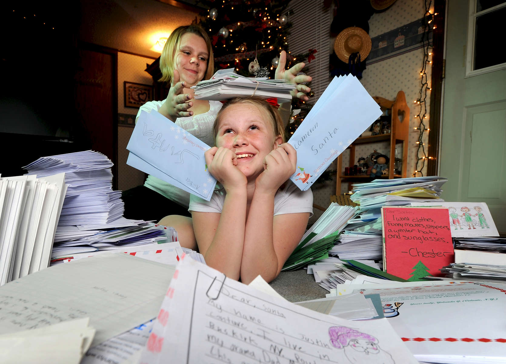 Jason McKibben - jmckibben@poststar.comJustice White Sloan, 10, front, and her sister, Bethany, 13, pose Tuesday, November 30, 2010, with some of the thousands of letters to Santa Claus they have received this year. The letters will be given to Macy\'s which has pledged to donate a dollar for every letter, up to 1 million, to the Make-A-Wish Foundation. This is the second year Justice, who has a genetic disorder that causes liver and lung problems, spearheaded a letter campaign. Last year she collected 10,000 letters.