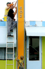 Dawn Surak and her brother Alan Laskowski paint letters on the sign of their Lucky Dog Diner in Venice, Florida, as Surak's son Ollie, 4, plays below them .