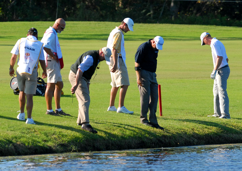 Vaughn Taylor, right, searches for his ball after hitting it near the water on the 17th fairway during the third round of the Children's Miracle Network Classic golf tournament at Walt Disney World in Lake Buena Vista, Florida.