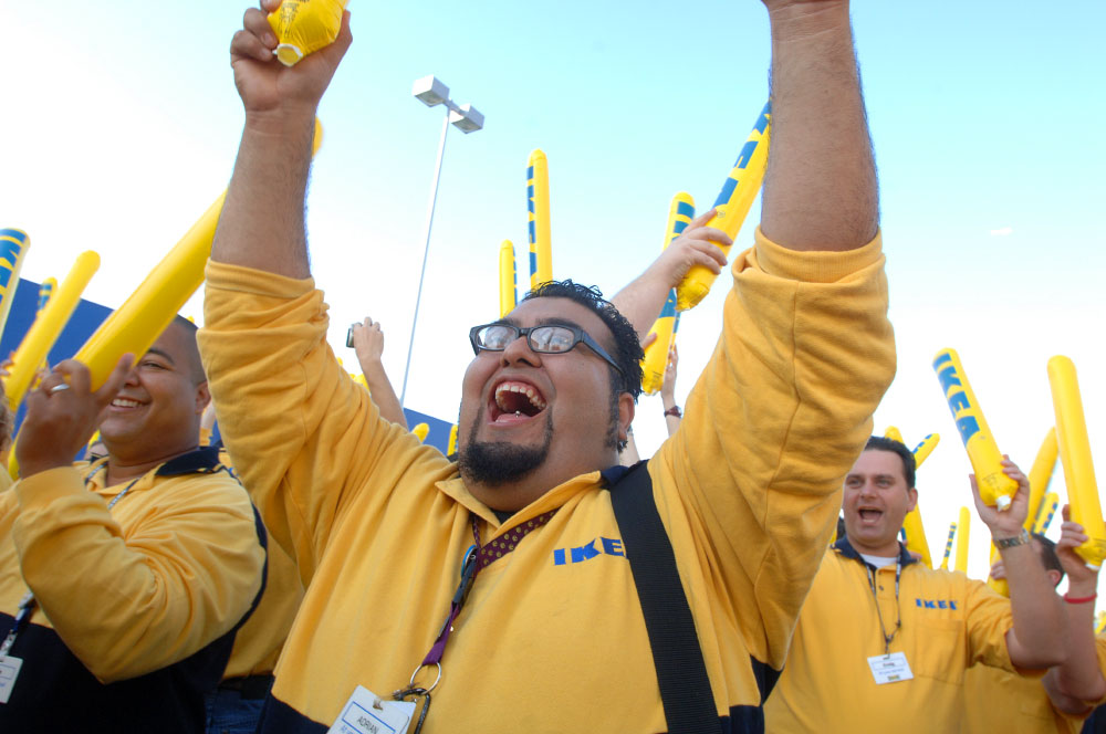 Employee Adrian Gonzalez, center, of Burbank, Calif., helps pump up the crowd waiting to enter the new IKEA store during grand-opening ceremonies in Orlando, Florida.