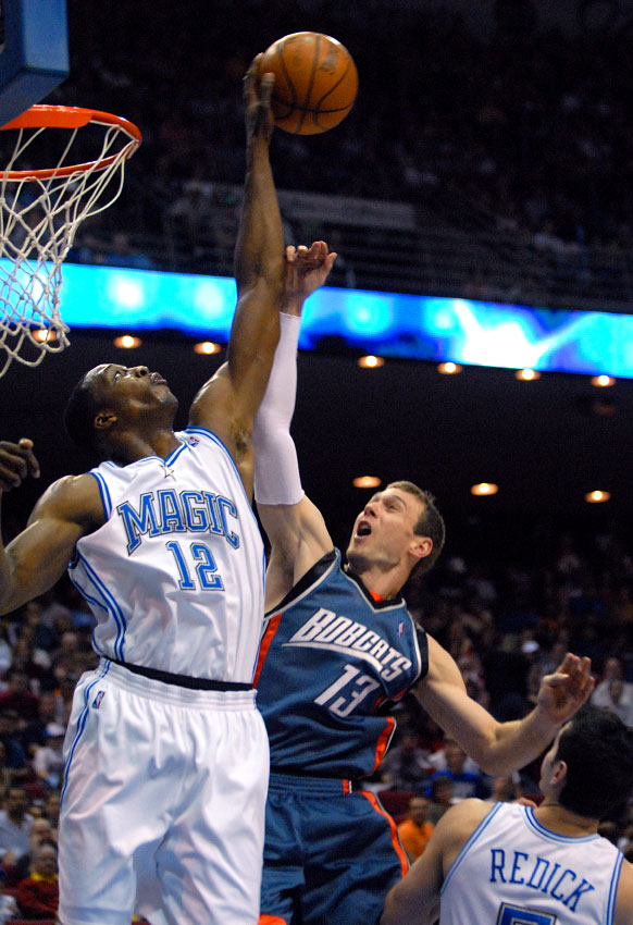 Orlando Magic center Dwight Howard, left, blocks a shot by Charlotte Bobcats guard Matt Carroll as J.J. Redick watches during the first half of their basketball game in Orlando, Florida.