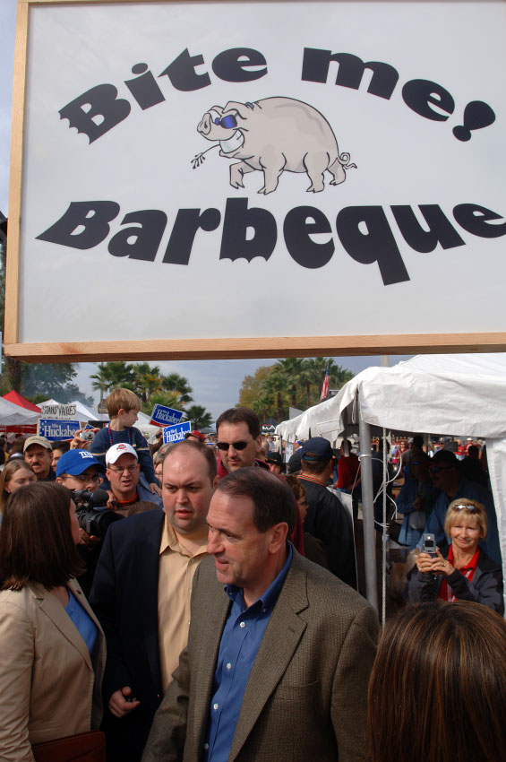 Presidential hopeful and former Arkansas Gov. Mike Huckabee, center, walks through the various barbeque meat booths at the Lakeland Pig Fest while campaigning in Lakeland, Florida.