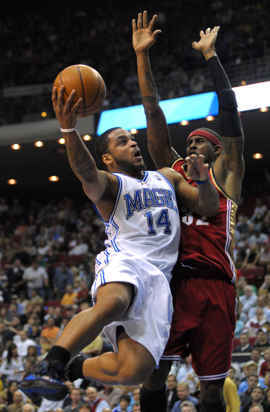Orlando Magic guard Jameer Nelson, left, drives to the basket in front of Cleveland Cavaliers guard Larry Hughes during the first half of their NBA basketball game in Orlando, Florida.