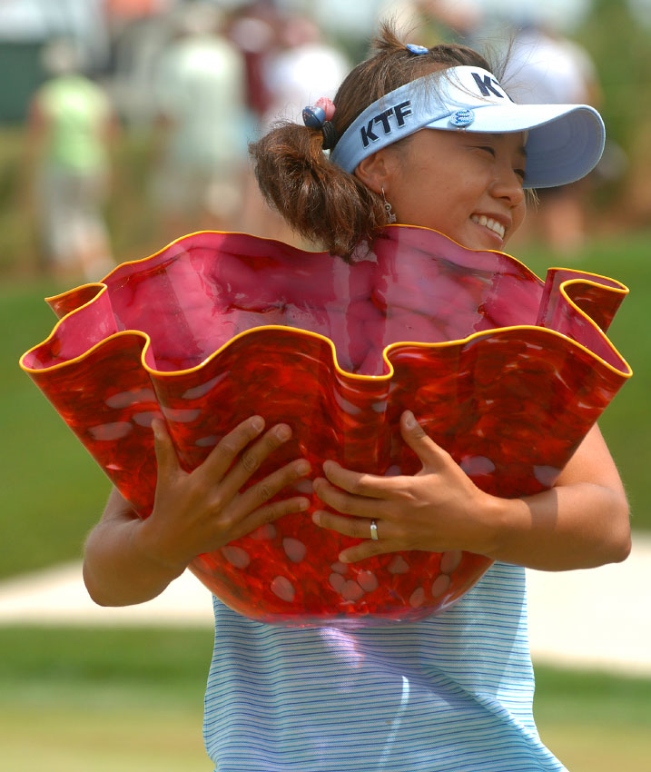 Mi Hyun Kim, of South Korea, hugs the championship trophy after winning the Ginn Open LPGA golf tournament with a score of 12-under-par, 276, in Reunion, Florida.