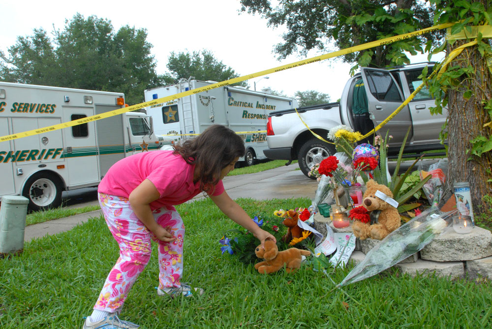 Alexandra Ortiz, 6, of Sanford, Florida., places a stuffed animal onto a makeshift memorial outside the home where Franklyn Duzant is alledged to have killed his son and wife in Lake Mary, Florida.