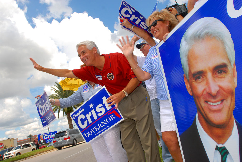 Florida Republican gubernatorial candidate Charlie Crist, center, waves to passing motorists outside the Mall at Millenia in Orlando, Florida.