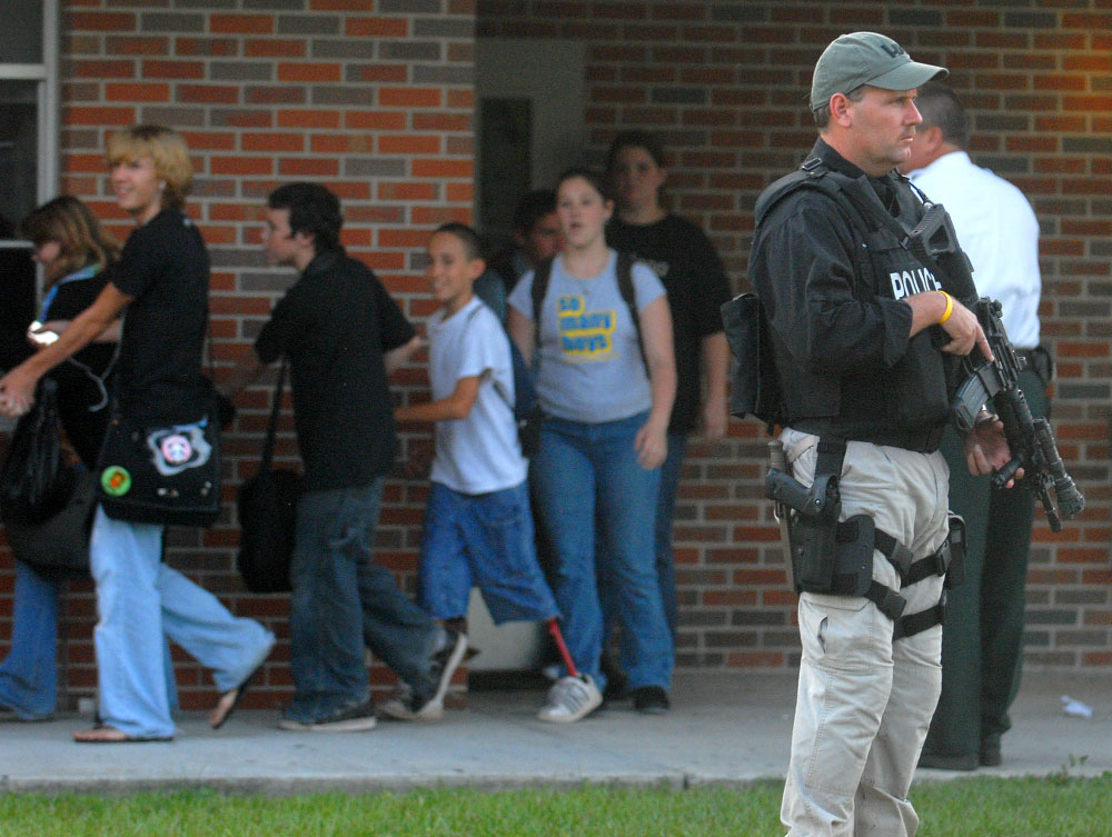 A police officer stands guard as Kathleen High School students are escorted away from the campus, which was in lockdown mode while police searched the premises for a fugitive murderer.  The school is near an area where two fellow deputies and a police dog were shot after a traffic stop in Lakeland, Florida.