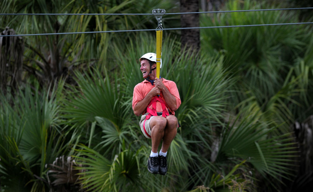 A rider holds on tight while gliding along on a zipline at Forever Florida in St. Cloud, Florida.