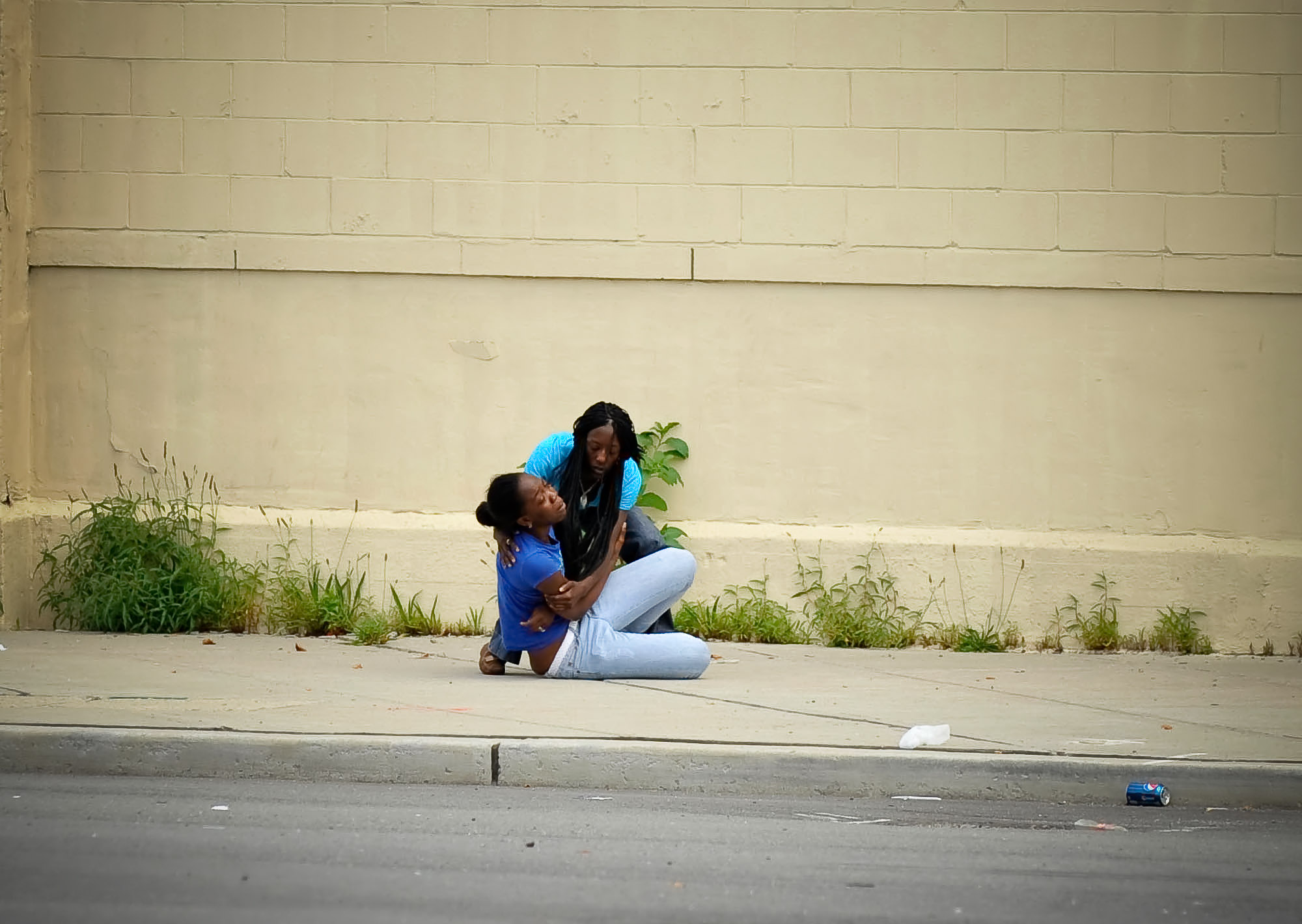 The daughter of a shooting victim collapses in a friend's arms on Elizabeth Ave after hearing her mother was murdered during a drive-byshooting at Meeker and Elizabeth streets in Newark, NJ.