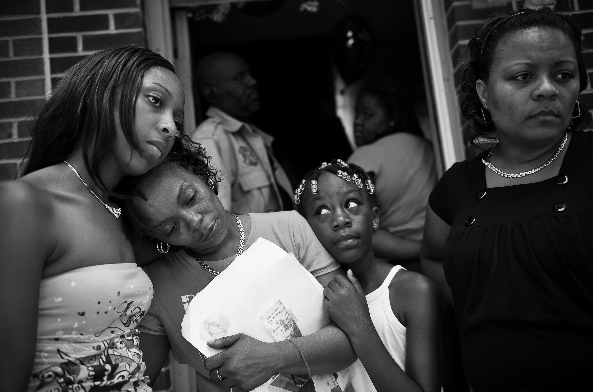 Sharonda Melvin, the mother of a 17 year old killed Saturday at MLK Blvd and Kinney St. in Newark, NJ is comforted at home Sunday afternoon surrounded by family members Angela Gainer (left), Chante Gedeon (center) and Sharon Melvin (right).   Photographed for The Star-Ledger