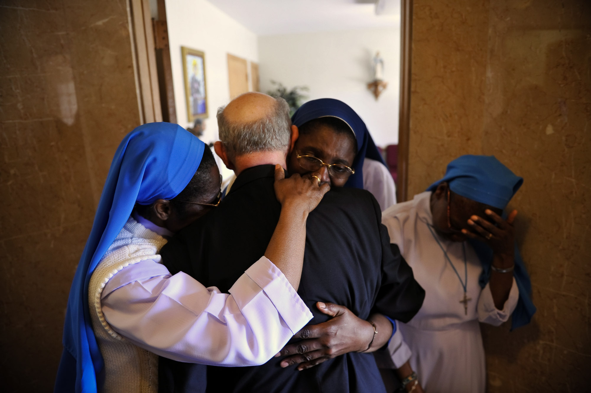 The nuns,  Sr.Mary Henrietta Iroghumg, Sr. Mary Victur Egbokg, Sr. Mary Victoria Loeka and Sr. Mary Obi Oraka say their goodbyes and embrace Msgr. Granato near the front door of the Rectory as he exits Tueday after Mass.  The Last mass celebrated by Msgr. Granato at St. Lucy's Church, Newark is held Tuesday morning. The monsignor, who is 80 and spent 54 years at the church, he must move out upon the orders of the diocese of Newark.   Photographed for The Star-Ledger