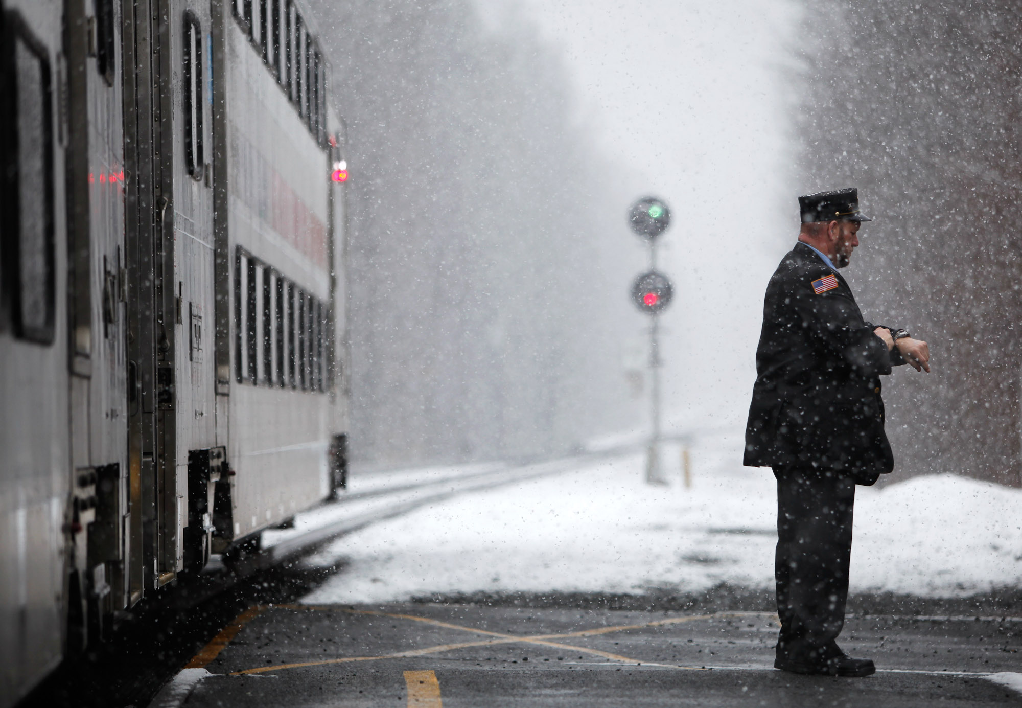 A NJ Transit Conductor checks his watch as the 7:10am train readies to leave High Bridge station.