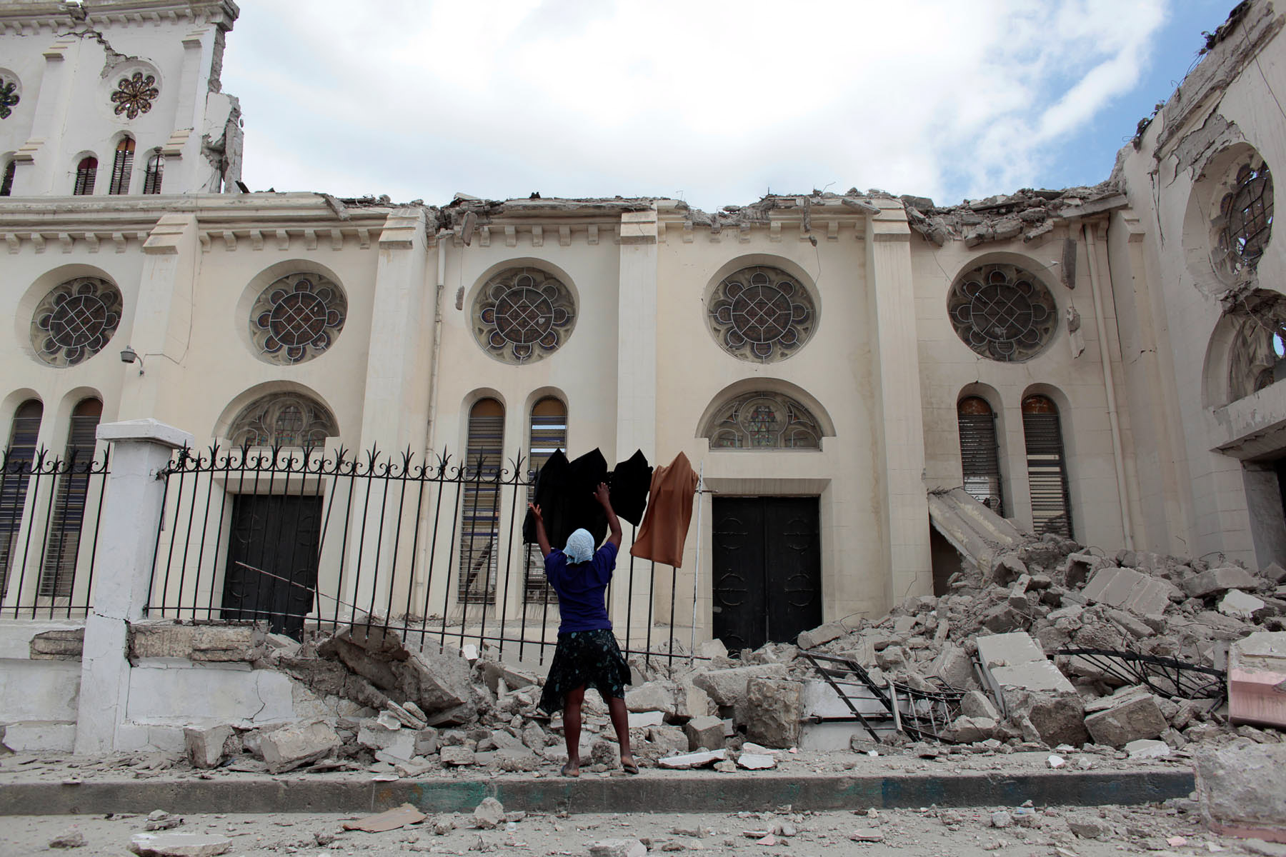 Marie Loude hangs laundry on the fence surrounding the destroyed Cathedral in Port-au-Prince following the 2010 earthquake that struck the Island nation.   Photographed for The Star-Ledger