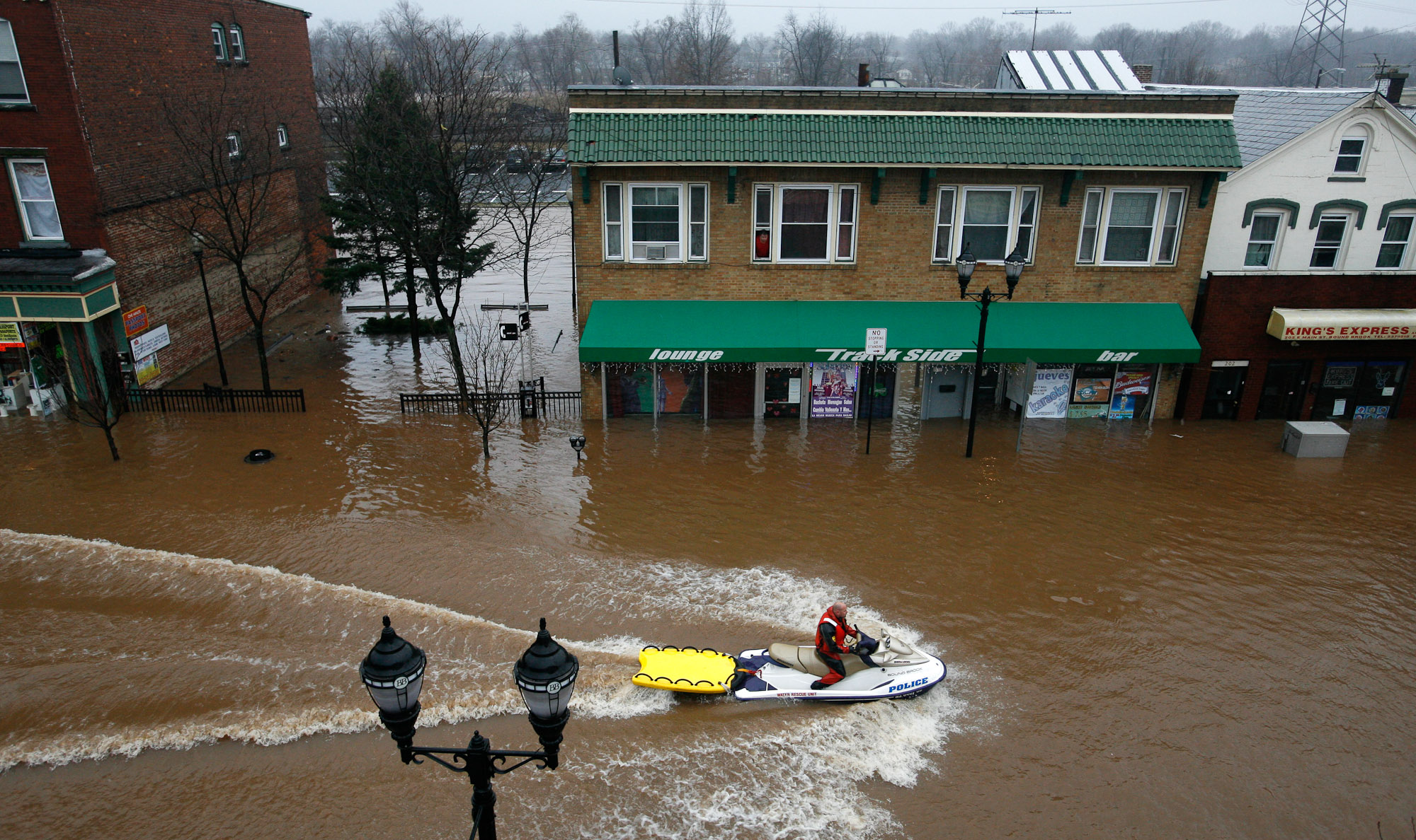 A Bound Brook Police Officer  rides down Main St. in Bound Brook, NJ looking for residents to be evacuated.  Residents evacuate and are rescued by Bound Brook Police and Rescue Squad and Somerset County Dive Team in  Bound Brook as the Raritan River rises from heavy rains. Photographed for The Star-Ledger