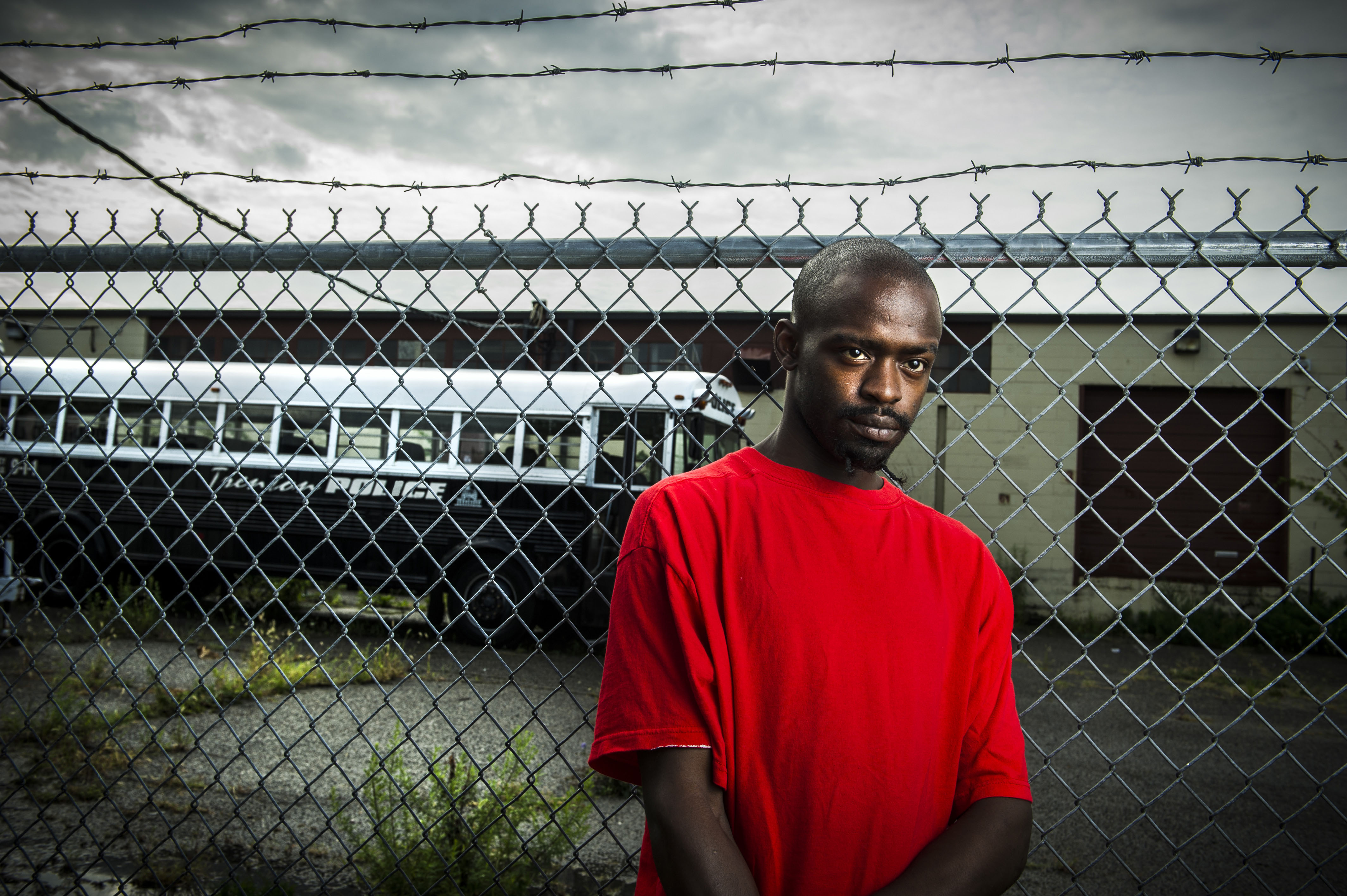 Patrick, a homeless man and artist,  has struggled to stay out of trouble. He stands just outside the barbed wire fencing surrounding the Trenton Police Dept.  Photographed for the Trenton Health Team