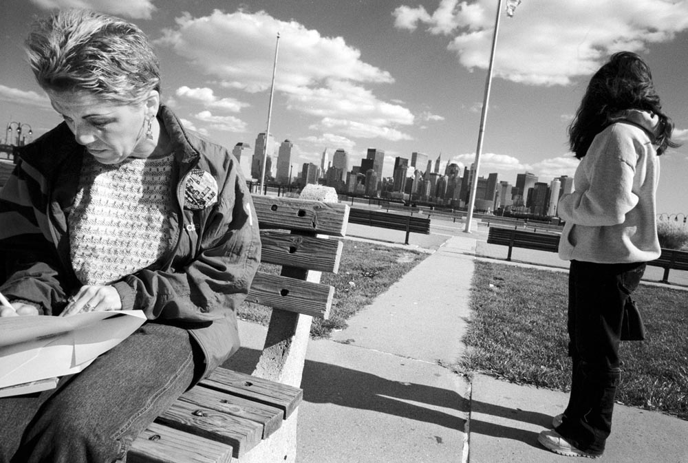 At Liberty State Park in Jersey City, NJ, Lois writes a card to Michael which she will leave a the wall of memory at {quote}Ground Zero.{quote}  Her daughter Jeannette looks accross the Hudson River to lower Manhattan's new skyline.  {quote}I used to send him cards for everything,{quote} Lois says.  {quote}This is the last card I will send him.{quote}
