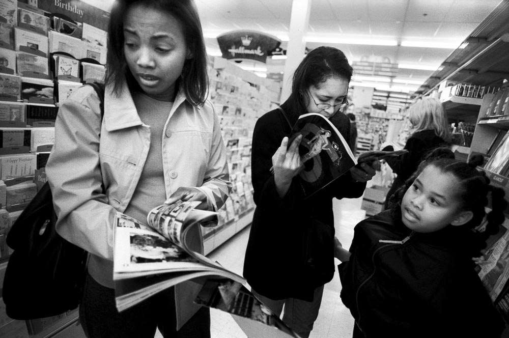 While shopping with her friend Yvette and Yvette's daughter, Sharon turns away after seeing her own family photograph in a magazine feature about September 11th.