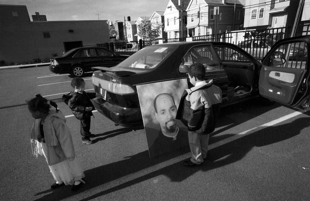 Following yet another memorial service, the children wait for Sharon to arrive at the car to go home. Young Sean stands before a picture of his late father.