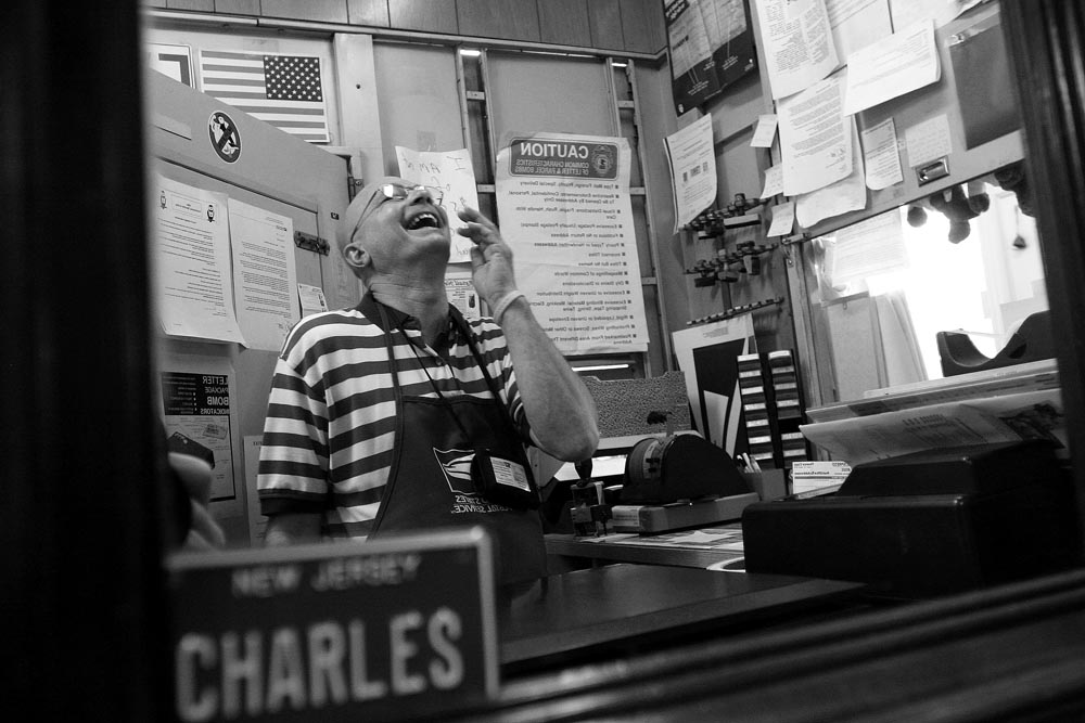 Reflected in a small mirror with a bicycle name license plate affixed to it with his name, Sergeantsville Postmaster Charles McGill laughs as he assists  customers  at the counter in the post office at 557 Route 604 East (Rosemont-Ringoes Road) .