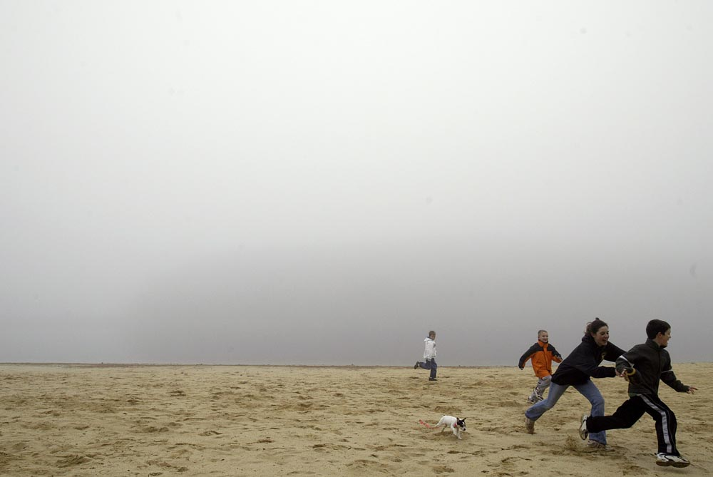 Heavy fog hangs in the air above Round Valley Reservoir Wednesday afternoon.  Playing some football on the beach after a half day of school are Samantha Beadle (age 13), Ryan Beadle (age 7), Brandon Puc (age 7) and Max Mead (age 7).  Callie the dog chases after the kids. Photographed for The Star-Ledger