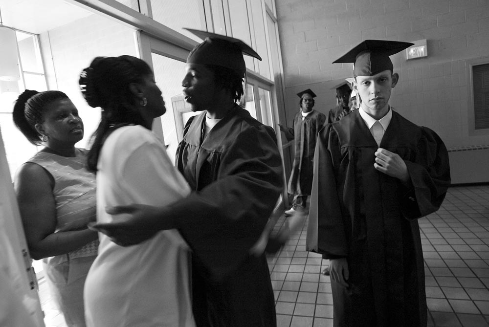 Valedictorian David Tingoli (right) spends the last few minutes before graduation alone, as his classmate Ronnie Davis (center) greets family members entering the school.  Tingolie , a loner spent 4 years at the school after being thrown out of standard public school in Orange due to violent behavior.  In October, 2004, Davis was shot in the head and killed  during a dispute over a woman.