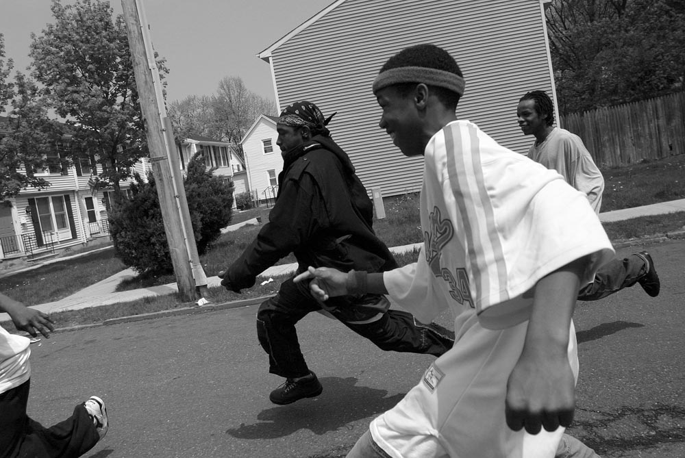 Although the school's staff constantly tell the students not to run outside the school,  Al Malik Collins (center, left) and other students chase each other down the street.  For them, it is a way to release excess energy, but to neighbors it means something else.  Neighbors often call the police because they fear the kids are engaged in criminal activity.