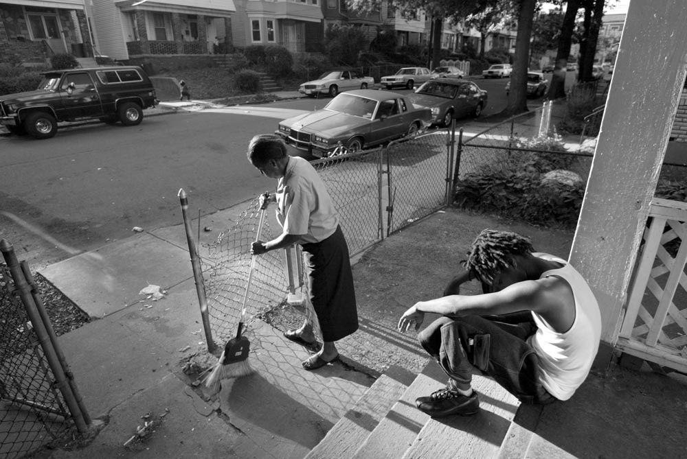 Tamar Bowman's grandmother Barbara sweeps up the area in front of their home on Seymour St. after coming home from work.  Tamar, who has just awoken, sits on the steps as Barbara sweeps.  Barbara is upset that she comes home from a day's work to find the area filthy. She is the only member of the Bowman family with a job.