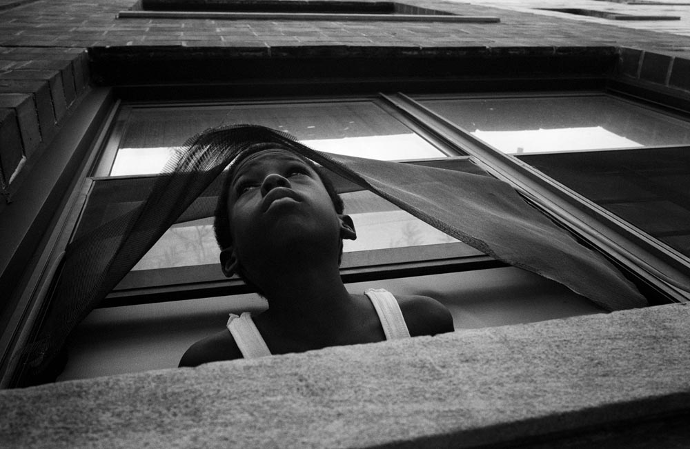 Maurice, who lives with his mother Peaches in a Newark housing unit peeks out of his window through broken screen to watch the demolition of other housing units accross the street from him.