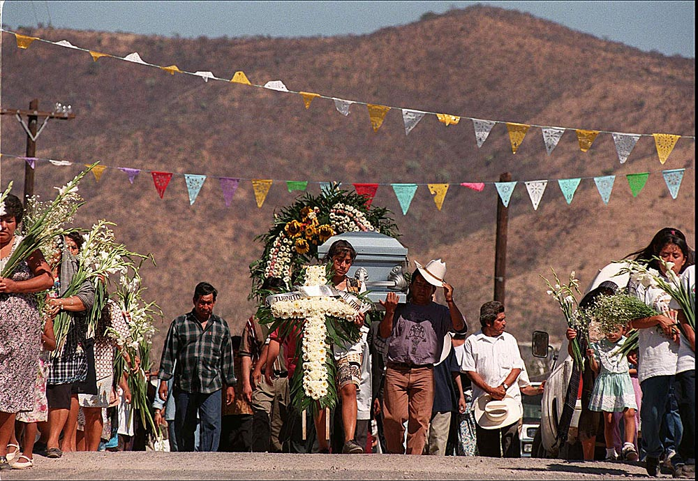 The villagers of Ahuehuetitla, Mexico move through town enroute to the cemetery on the edge of the village to bury 14 year-old Juan Manuel Calixto with his paternal grandmother. The teen was shot and killed in Passaic, NJ defending a fellow gang member. His family flew him home for burial.  Photographed for The Star-Ledger