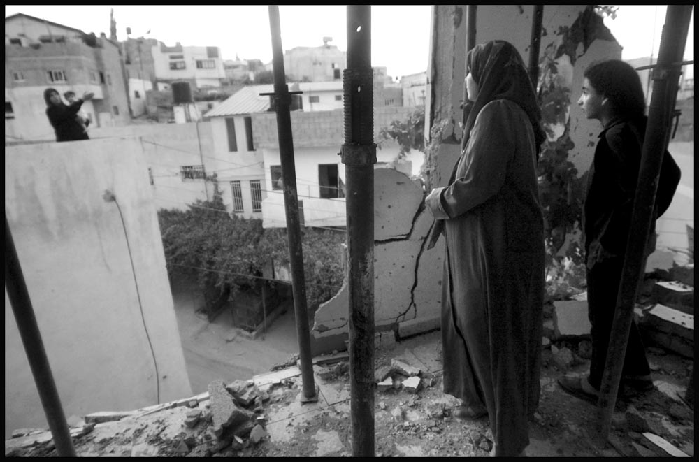 Sejoud Toubasi and her mother Aida talk with a neighbor through the destroyed third floor wall of their home in Jenin Camp on the West Bank.  The camp was devistated during fierce fighting between Palestinians and Israeli forces in April 2002.