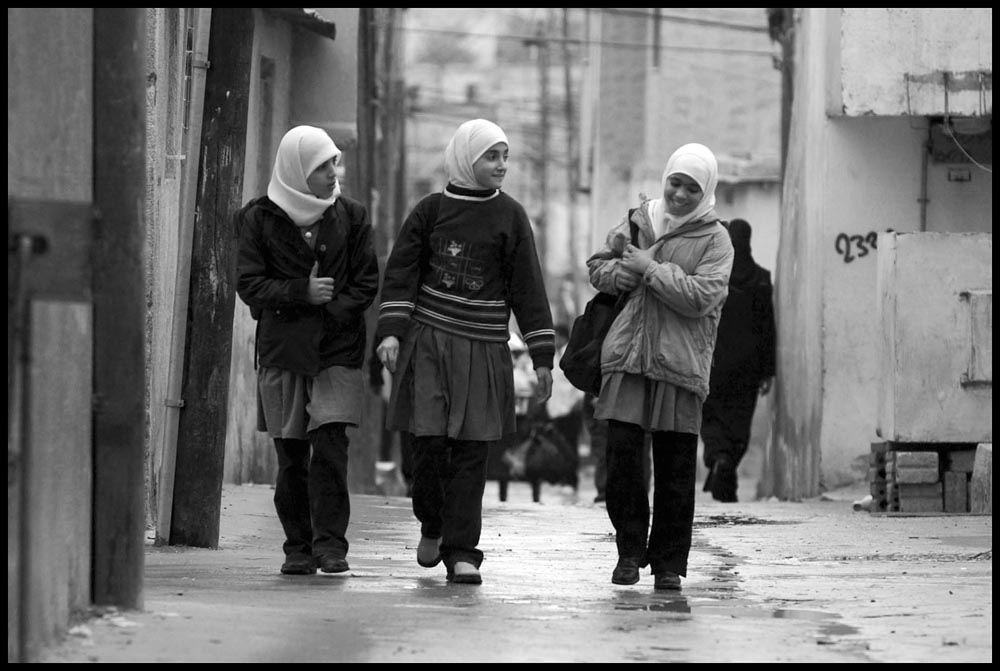 Three young girls walk to school in the Baqaa Palestinian Refugee Camp near Amman, Jordan.  The camp contains approx 150,000 refugees and is the largest of the 19 official refugee camps in the Middle East and the largest of 9 in Jordan.  Jordan has been placed in a difficult position by U.S. foreign policy in the it is geographically located between Israel and Iraq and has to cope with the Israeli/Palestinian issie and the possible U.S. led invasion of Iraq.