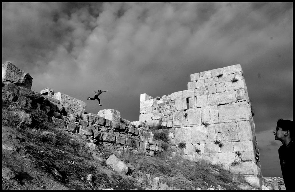 Nine year-old Sali Samir Asan Sahin jumps from ancient rock to ancient rock at the top of a hill where the Roman Temple of Hercules, 2nd century A.D. rises in ruin in the center of Amman, Jordan.  She lives nearby and plays of the rocks often.