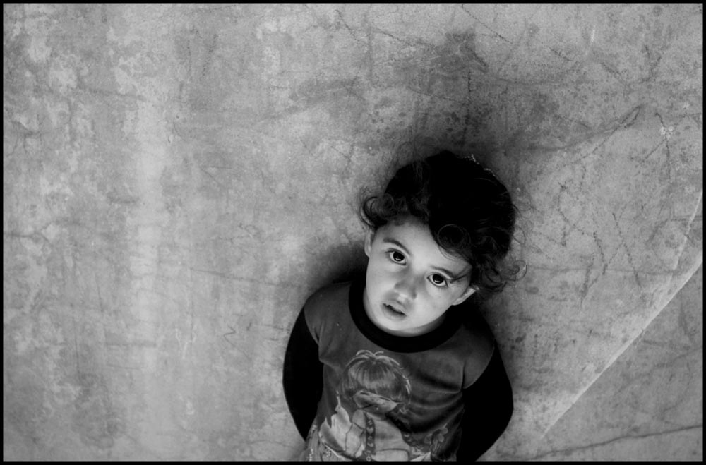 A child stands in the hallway of a squalid residential building in Gaza City.