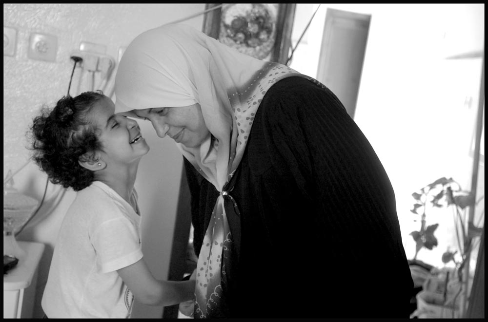 Seven year-old Saja Toubasi laughs with her mother Aida inside the Toubasi home in Jenin Camp on the West Bank.