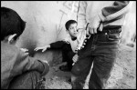 Eleven year-old Suleyman Semsiya grabs the pant leg of his friend Kadir Aktas who holds a toy gun. The chidlren warm themselves in an alley with their friend Recep Uran.  {quote}Of course we'll have real guns when we grow up..{quote} Kadir says, {quote}...in case there is a fight.{quote}