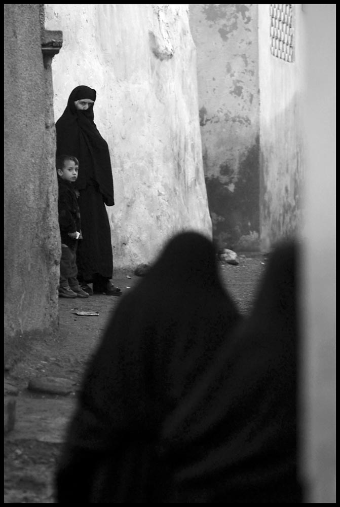 A woman and her son watch other Muslim women walk along a street in Silopi, Turkey, a town along the border with Iraq. The town holds what is said to be the grave of Noah, builder of the biblical ark.