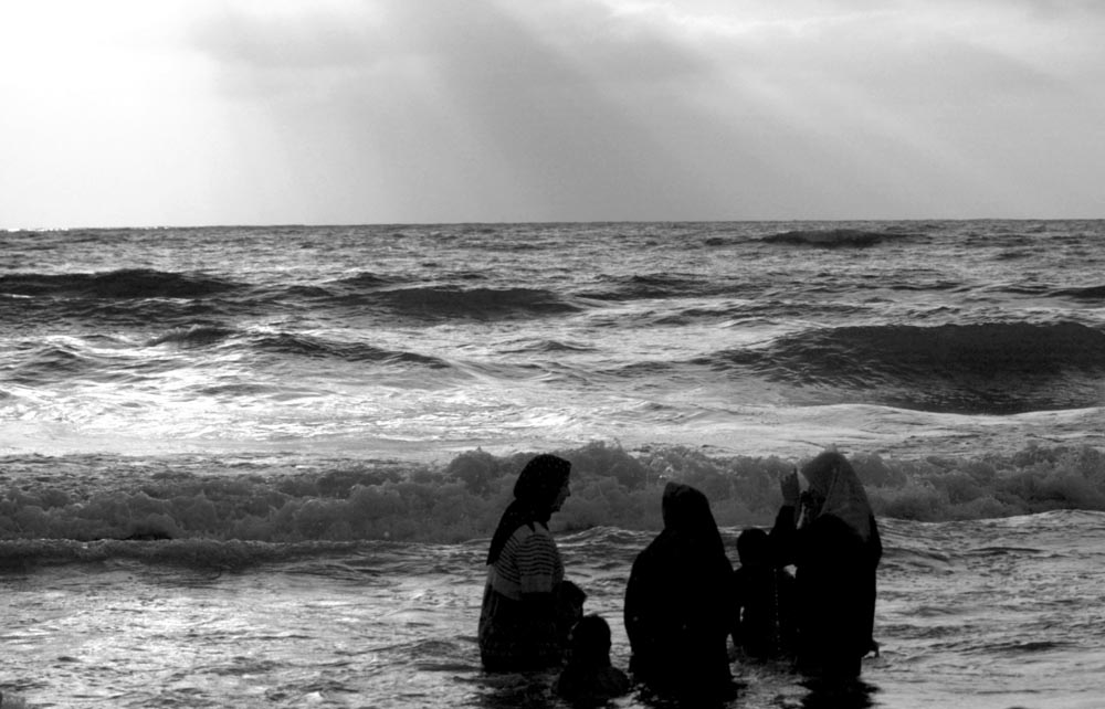 Women and their children enjoy the Mediterranean Sea in Gaza.