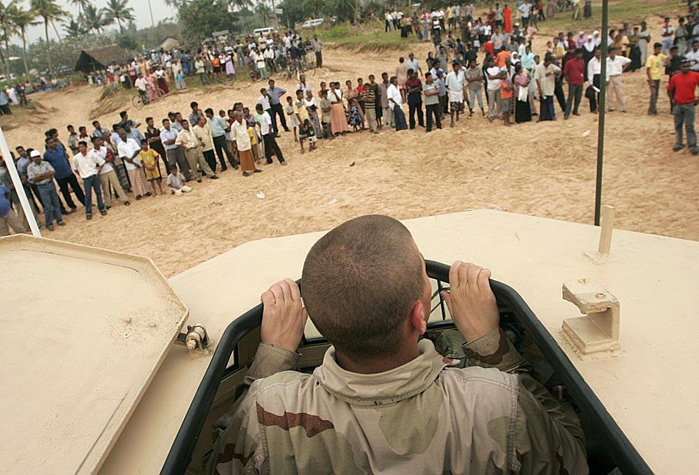 US Navy Seaman Brandon Marks of Kansas City, KS peeks his head through the top of an Amphibious vehicle to look out at the hundreds of Sri Lankans gathered on the beach in Galle to watch the landing of the soldiers to help with relief efforts on the island following a devestating Tsunami.   Photographed for The Star-Ledger