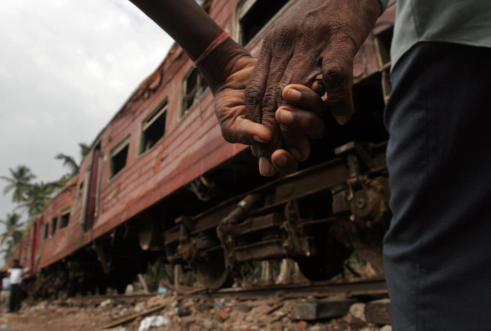 A man and his son walk together Tuesday afternoon past the train which was swamped during the Tsunami in Southeast Asia.  More than 1,000 died in the train wreck.  Photographed for The Star-Ledger
