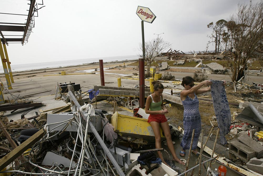 Boo Young and her daughter Jessica (age 14) clean clothing they found in the trees by using broken water pipes at a destroyed gasoline station accross the street from a destroyed Dennys on the beachfront in Biloxi, MS.   The family stayed at a nearby home further inland during the storm and returned to their home completely destroyed.  Photographed for The Star-Ledger