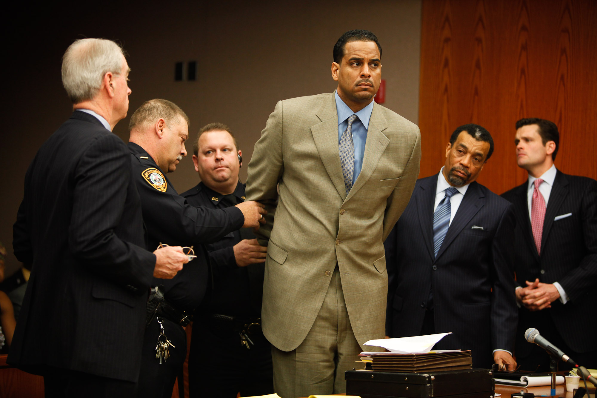 Jayson Williams is handcuffed by Somerset County Sheriffs Officers as he is taken into custody Tuesday, eight years and 10 days after he fatally shot his 55-year-old limousine driver Costas Christofi at his former Hunterdon County estate.Williams, 42 is  sentenced to at least 18 months in prison Tuesday as he appears before Superior Court Judge Edward Coleman.Mr. Williams appears with his attorneys Joseph Hayden and Billy Martin.Williams pleaded guilty Jan. 11 to a downgraded charge of aggravated assault under the terms of a plea agreement reached Dec. 24 with the State Attorney General's Office, which took over the case from the Hunterdon County Prosecutor's Office.Williams, who was awaiting retrial on a reckless manslaughter charge, also waived his right for post-conviction relief, a legal motion to set aside a conviction before filing an appeal.