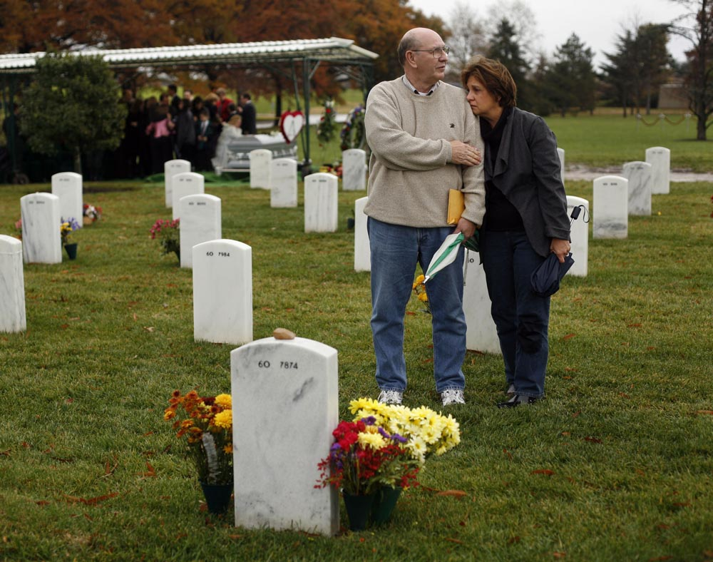 Frank and Judy Adamouski stand together at the grave of their son James in Arlington National Cemetery.   Parents of Black Hawk pilot killed in Iraq,  Frank  and Judy are one of an apparent increasing number of Gold Star families who turned to Freedom of Information Act to navigate their way through through the fog of a controversial war and the loss of loved ones.Capt. James Adamouski, 29, of Springfield, Va./Savannah, Ga.  died 04/02/03 in Black Hawk helicopter crash near Karbala Gap in Iraq.  He was piloting. The military account has changed from friendly fire to hostile fire to pilot disorientation. In days after the crash, his father had FOIAed the maintenance records....took more than a year for him to get them...now the theory is that it was friendly fire, based on his conversations with crew in other helicopter on the mission. The funeral for  CW4 John Priestner, Apache Pilot killed in Iraq, 182 Battalion, 82nd Combat Aviation Brigade has just ended behind them.  Photographed for The Star-Ledger