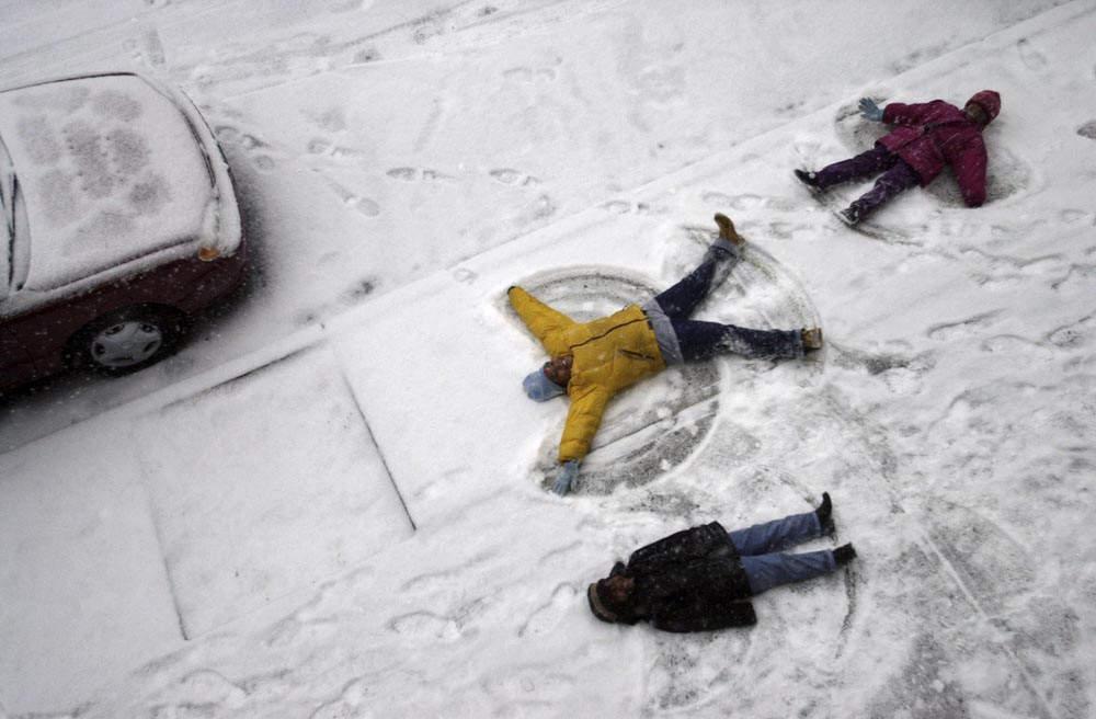 Making snow angels outside their building along Dr. Martin Luther King Blvd. in Newark, NJ  during a snowstorm are Shoataisa Jones (age 9),  Tamika Boynes (age 5) and Shanik Austin (age 6). Photographed for The Star-Ledger