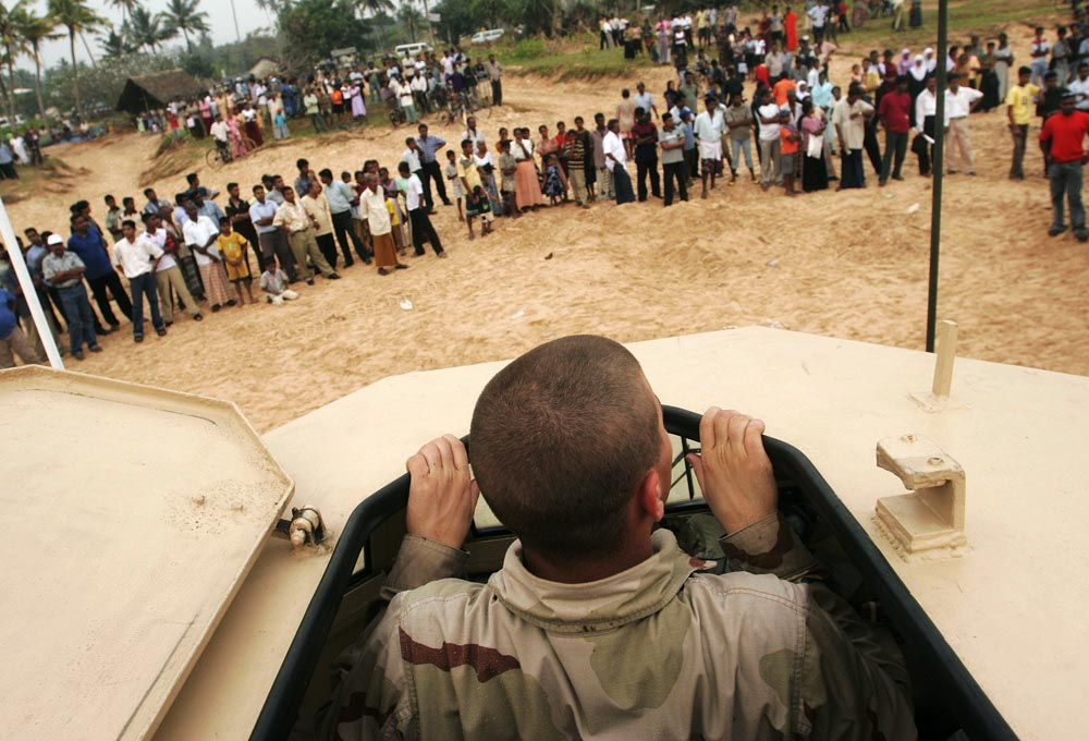 US Navy Seaman Brandon Marks of Kansas City, KS peeks his head through the top of an Amphibious vehicle to look out at the hundreds of Sri Lankans gathered on the beach in Galle to watch the landing of the soldiers.