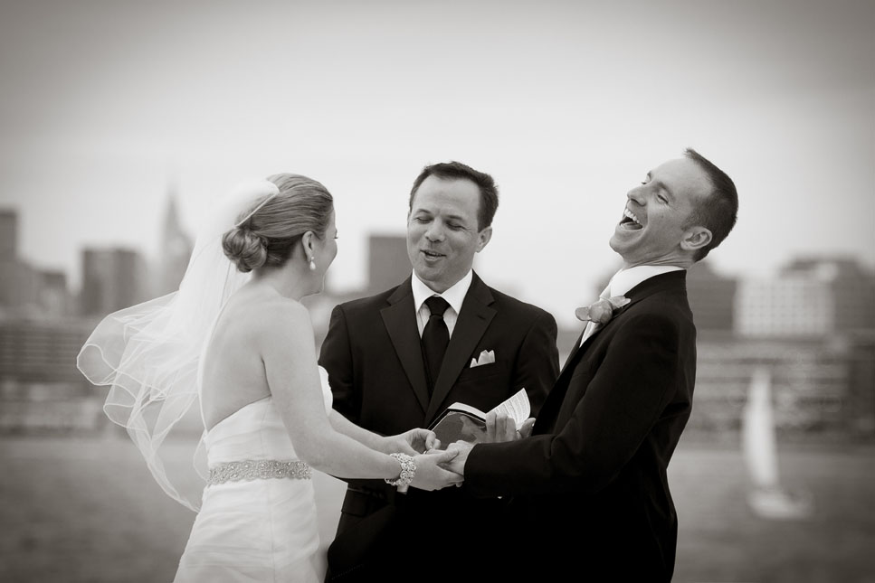 A photojournalistic wedding photo of a groom laughing during his wedding ceremony at the <u>Jersey City Hyatt </u></a>in Jersey City, New Jersey. An outside wedding ceremony features the New York City skyline as a background.