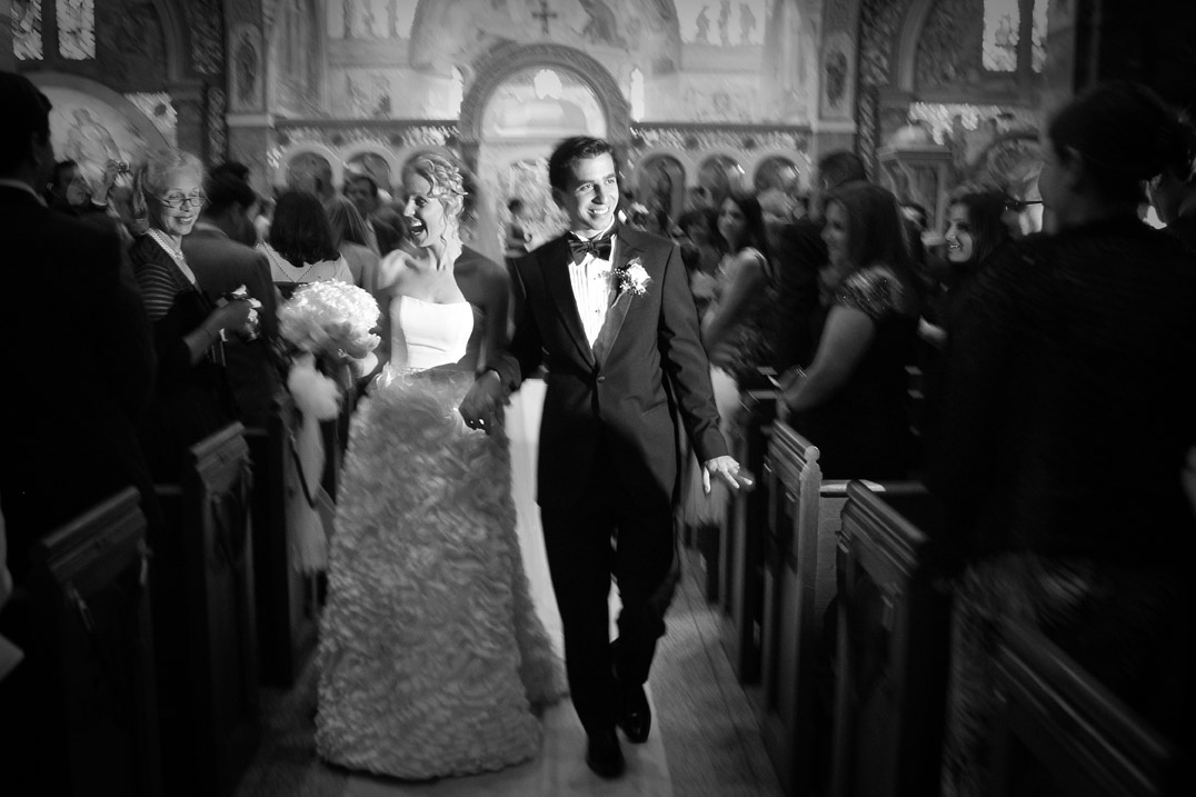 A photojournalistic wedding photograph of a bride and groom walk down the aisle at the Cathedral of Saint Paul in Hempstead, New York.