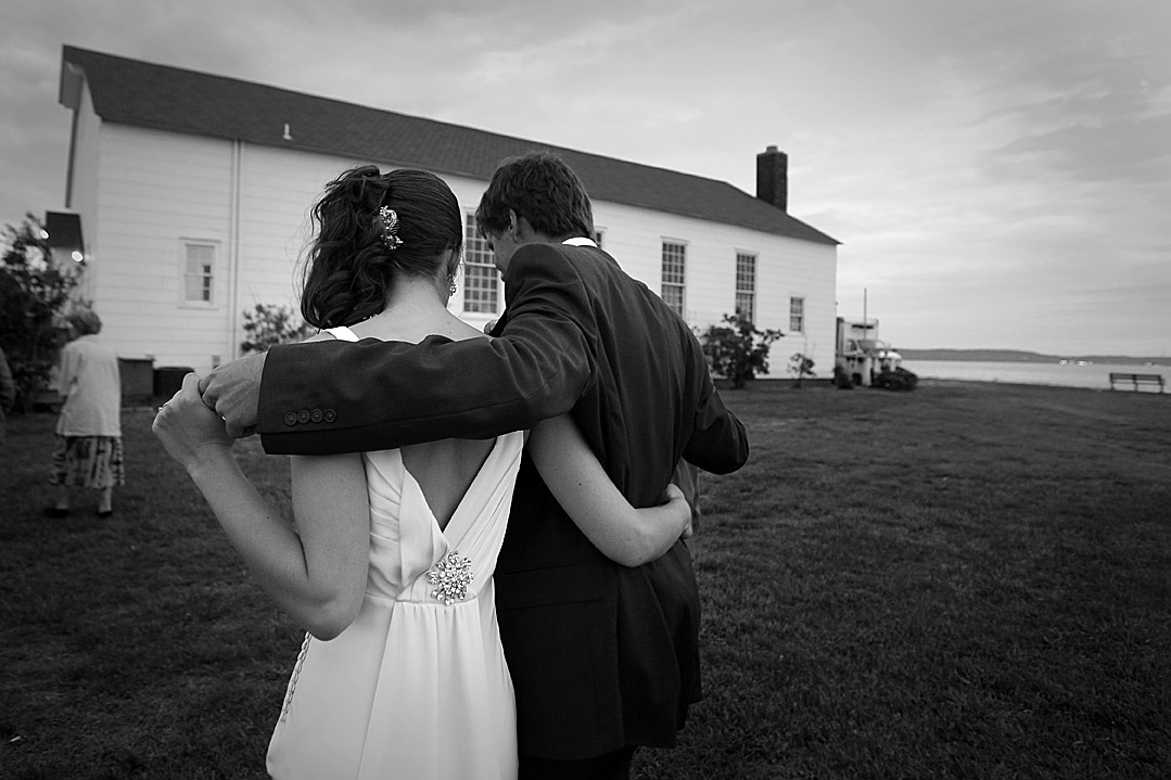 A bride and groom walk together at the Chapel at Sandy Hook, New Jersey.  A photojournalistic approach to wedding photography leads to candid wedding moments.