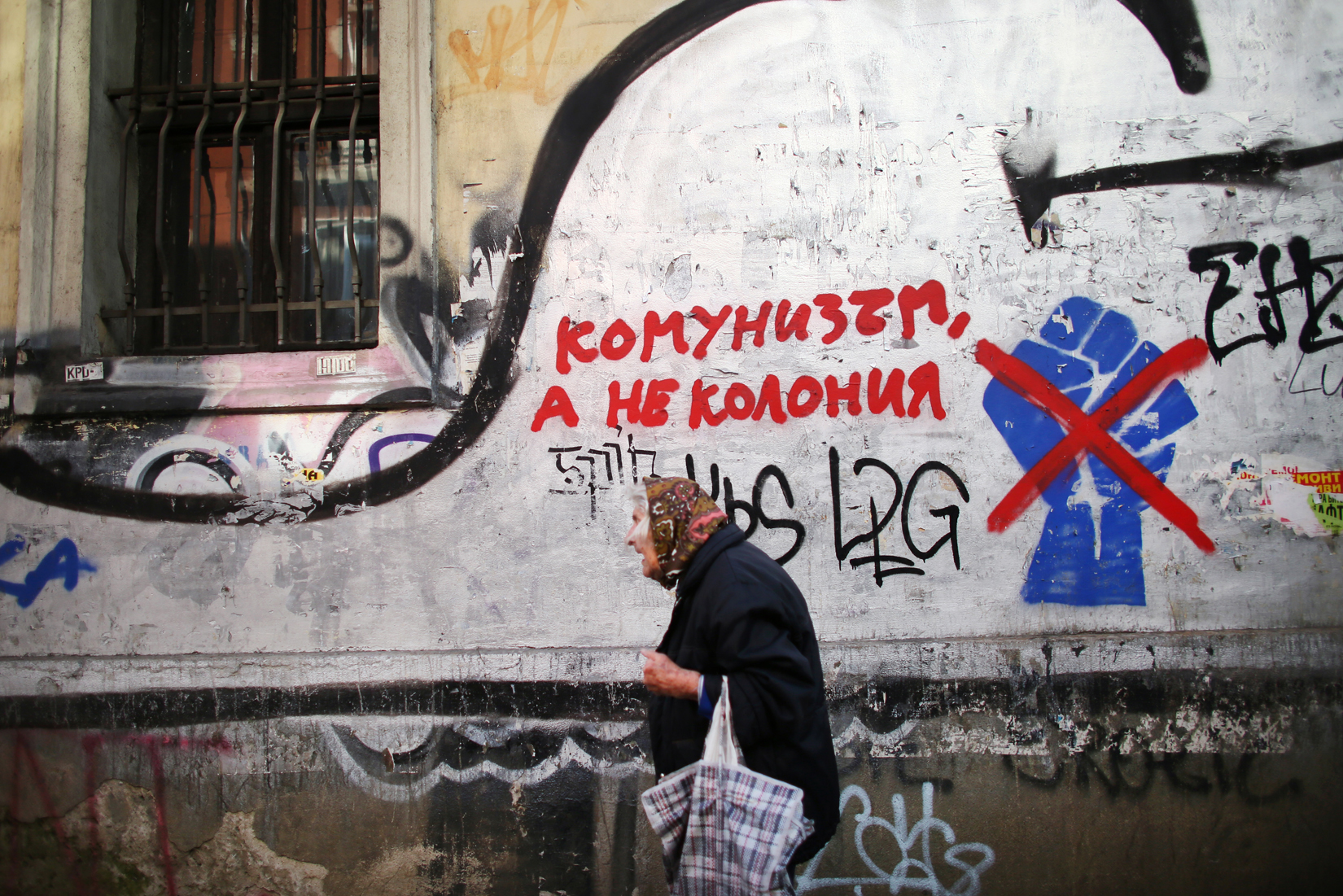 A woman walks by graffiti of the fist that came to symbolize civic protests against political corruption in 2013, seen in Bulgaria's capital Sofia, on October 4th, 2014. The fist has been crossed off by a second layer of graffiti, with an adjacent sign that reads, {quote}Communism, but not a Colony,{quote} in likely reference to what some political parties decry as Westernization of interests in the country. Bulgaria is still one of the poorest, most corrupt nations in the European Union, its post-1989 hopes wilted by political corruption, high crime rates and skyrocketing inflation. The ennui etches a permanent path across the average passerby's face, against a backdrop of rotting architecture, joblessness, and a vast population decline.