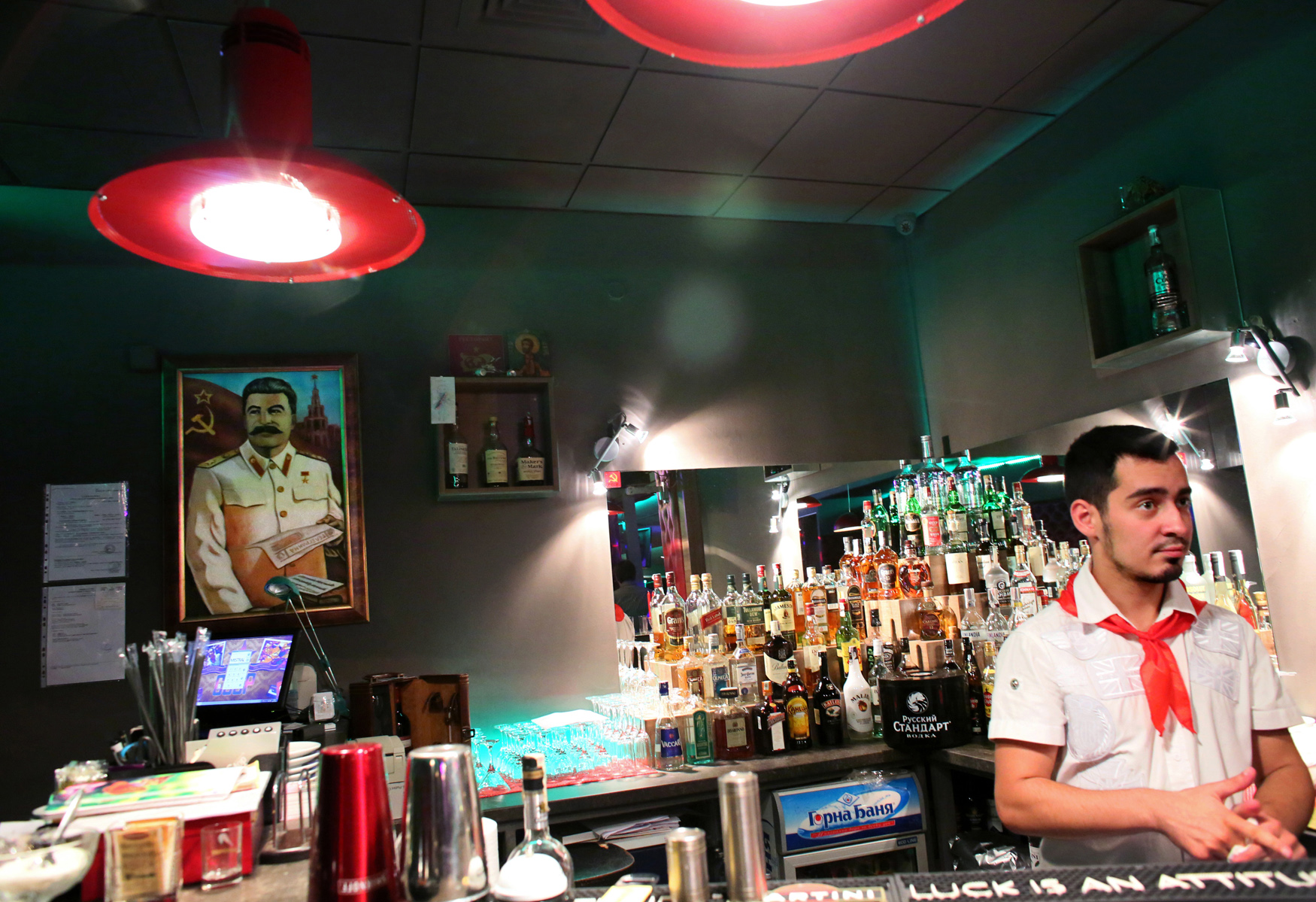 Kristiyan Stamatov serves drinks at SSSR, a USSR nostalgia restaurant and bar in Bulgaria's capital Sofia, in front of a portrait of Soviet communist leader Joseph Stalin, on October 4th, 2014. Stamatov is wearing a red tie, symbolic of what was once called a {quote}pionerche{quote} (pioneer,) or a Bulgarian student expected to serve the country and Communist party.
